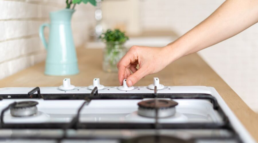 close-up of hand turning on burner on gas stovetop
